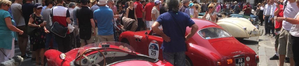 Et billede af en rød ældre sportsvogn i Italien med en stor folkemængde rundt om.